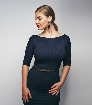 Portrait of confident female model posing against grey background. Plus size young caucasian woman.