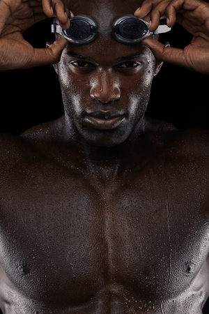Close-up shot of determined male swimmer with goggles looking at camera. Young african man with wet body. photo