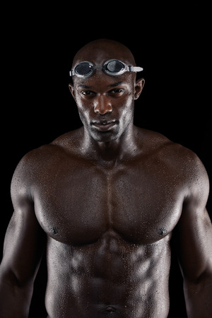 Strong and fit african athlete with wet body. Muscular male swimmer on black background. Young man with muscular build posing for camera. photo