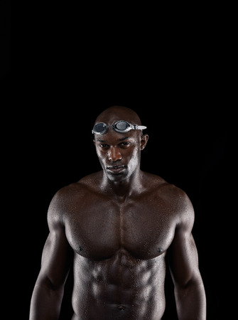 Portrait of strong young male swimmer posing for camera with copy space. African professional athlete with wet body against black background. photo