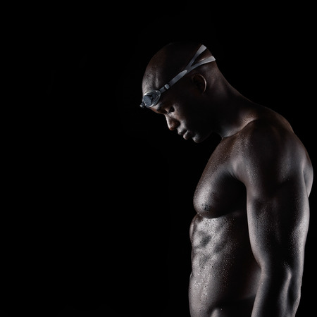 Side view of muscular young man wearing swimming goggles with wet body looking down over black background with copy space. Strong african male swimmer after training session. photo