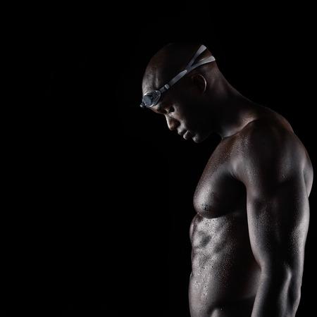 Vista lateral del hombre muscular wearing gafas de natación con el cuerpo mojado mirando hacia abajo sobre fondo negro con copia espacio. Fuerte nadador masculino africano después de la sesión de entrenamiento. Foto de archivo - 33458540