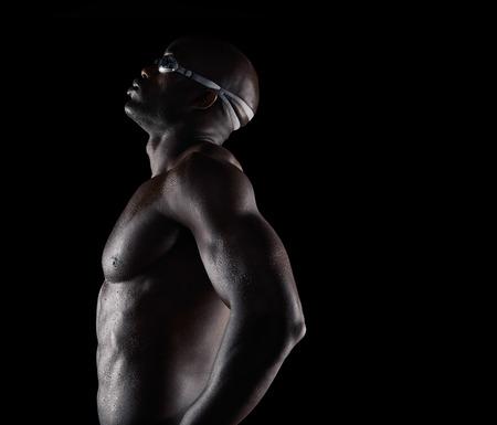 soustředění: Boční pohled na africké mužské plavec pauzu. Svalová mladý muž na černém pozadí s kopií prostorem.
