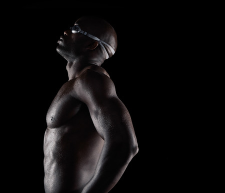 Side view of african male swimmer taking a break. Muscular young man on black background with copy space. Stock Photo