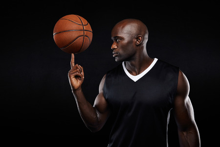 Portrait of young african athlete balancing basketball on his finger against black background. Focused basketball player. photo