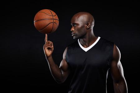 dedos: Retrato de joven africano de baloncesto de equilibrio atleta en su dedo contra el fondo negro. Jugador de baloncesto enfocada.