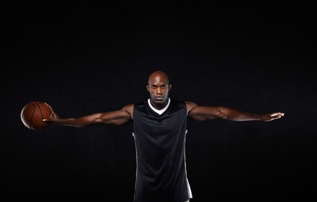 arm outstretched: Portrait of fit young man in sportswear holding a basketball standing with his arms outstretched against black background.