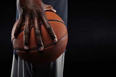 negras africanas: Primer plano de una mano del jugador de baloncesto sosteniendo una pelota contra el fondo negro. Foto de archivo