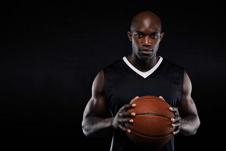 Portrait of professional african basketball player holding a ball looking at camera. Fit young man with basketball against black background with copyspace.