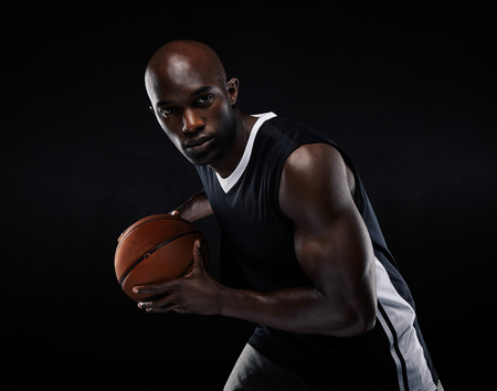Portrait of fit young male athlete playing basketball. African american basketball player against black background