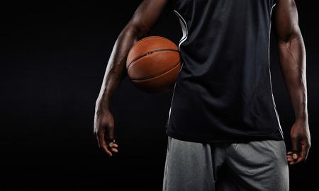 Recorta la imagen de jugador de baloncesto afro americano que sostiene una pelota contra el fondo oscuro Foto de archivo - 33676716