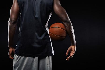 balones deportivos: Vista posterior de jugador de baloncesto africano con una pelota en el brazo contra el fondo negro con copyspace