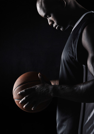 sport background: Side view of young african sportsman holding basketball against black background. Basketball player with ball.