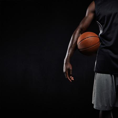Bijgesneden afbeelding van zwarte basketballer staan met een basket bal. Man in sportkleding bedrijf basketbal met copyspace op een zwarte achtergrond. Stockfoto