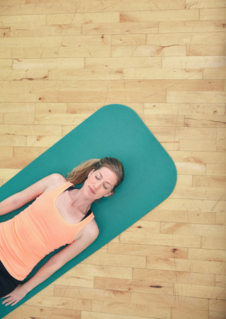 Top view of woman relaxing on yoga mat with copy space. Fitness female lying on exercise mat at gym. photo