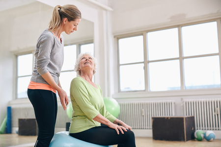 two woman: Portrait of a female gym instructor helping an older woman. Portrait of female coach assisting senior woman exercising in health club.