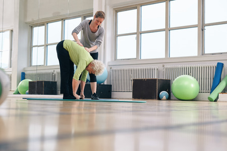 Senior woman bending forward and touching her toes being helped by personal trainer at health club. Elder woman doing back exercise with help from physical therapist at gym. Stock Photo