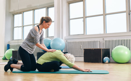 bend over: Female trainer helping senior woman to bend over. Old woman doing yoga on a exercise mat with physical therapist helping at gym.