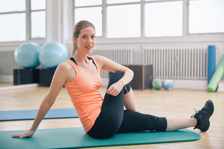Portrait of fit woman sitting on exercise mat warming up at gym. Woman stretching preparing for workout at health club. Stock Photo