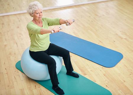 シニアの女性のフィットネス ボールの上に座ってダンベルを持ち上げます。歳の女性は、ジムでウェイトと運動。