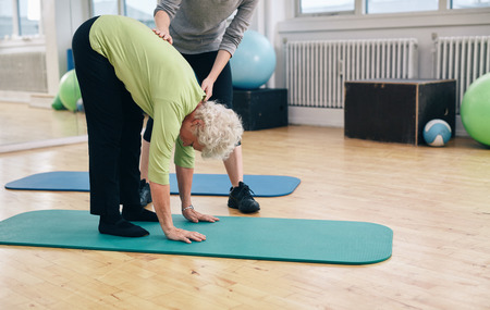 bending forward: Senior woman bending forward and touching her toes being helped by gym instructor. Elder woman doing back exercise with help from physical therapist at gym.