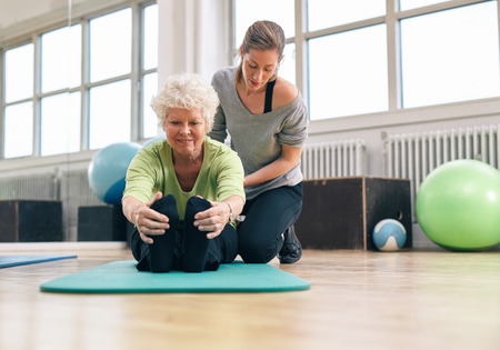 personal: Elderly woman being helped by her instructor in the gym for exercising. Senior woman sitting on fitness mat bending forward and touching her toes with her personal trainer assisting.