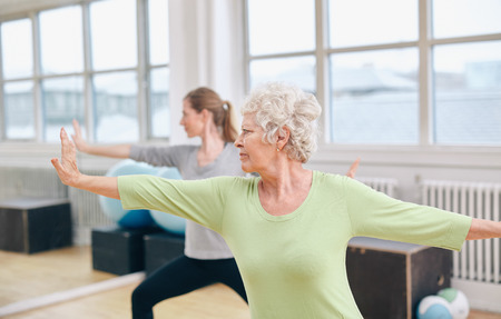 Two women doing stretching and yoga workout at gym. Female trainer in background with senior woman in front during physical training session Foto de archivo