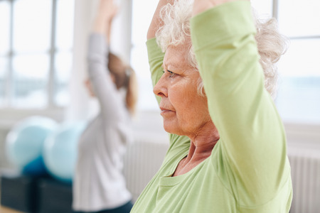 Close-up beeld van senior vrouw het beoefenen van yoga op gymnasium. Actieve senior vrouw te oefenen op de gezondheid club met vrouwelijke trainer in achtergrond.