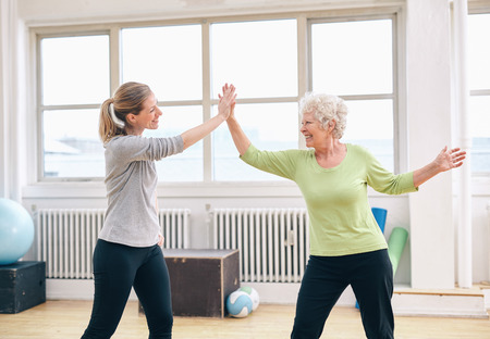 hands high: Senior woman giving high five to her physical therapist at rehab. Happy elderly woman celebrating fitness success with her instructor at gym.