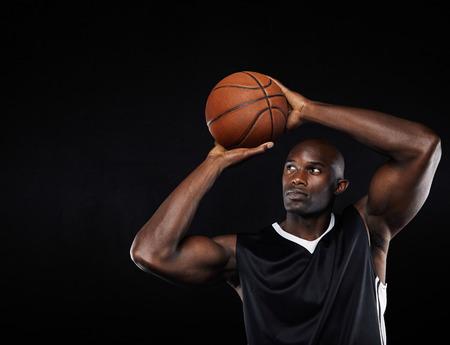 hombre disparando: Tiro americano jugador de baloncesto masculino africano joven en el aro contra el fondo negro