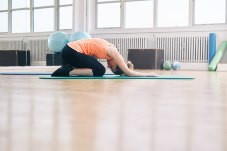 yoga studio: Portrait of woman doing a forward bend yoga exercise. Fitness woman practicing yoga at gym. Balasana - Child pose. Stock Photo