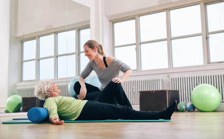 old people: Senior woman having a friendly chat with her personal trainer while exercising at gym. Elder woman doing pilates with gym coach.