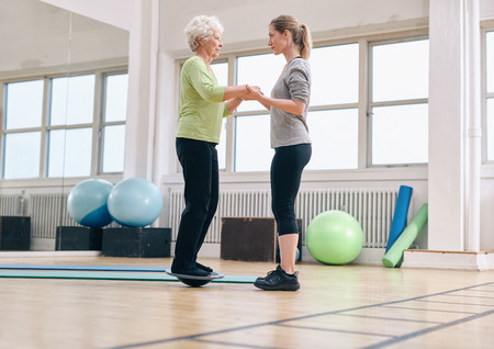 Female trainer helping senior woman standing on a balance board at gym. Elder woman exercising being assisted by personal trainer.