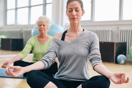 Women relaxing and meditating in their yoga class at gym. Female trainer performing a yoga routine with her class.