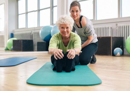 年配の女性が前方へ曲げを支援彼女のパーソナル トレーナーと彼女のつま先に触れる運動マットの上に座って。フィットネス コーチとジムでトレー