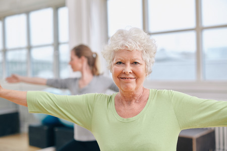 old people: Two women doing stretching and aerobics workout at gym. Senior woman with her trainer in background during physical training session Stock Photo