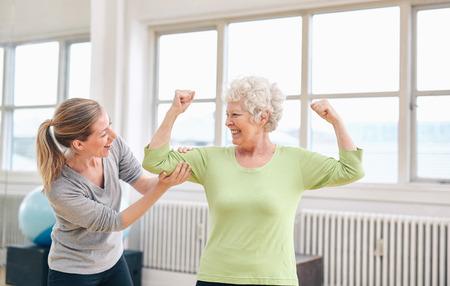 aide à la personne: Portrait de l'entraîneur femme regardant femme âgée fléchissant ses biceps au centre de réadaptation. Heureuse de sa récupération à la réadaptation.