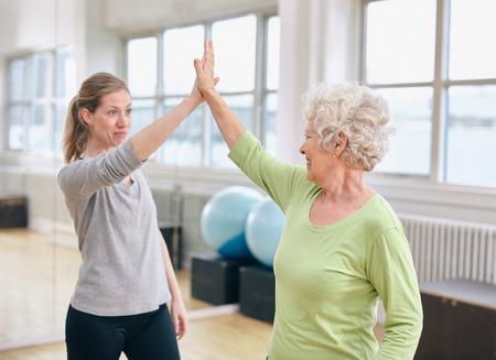gimnasio mujeres: Mujer mayor que da de alta de cinco a su entrenador personal en el gimnasio. Mujer mayor emocionada que disfruta de �xito en salud con su instructor en rehabilitaci�n.