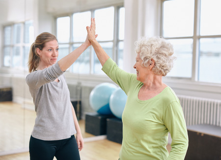 five people: Senior woman giving high five to her personal trainer at gym. Excited old woman rejoicing health success with her instructor at rehab.