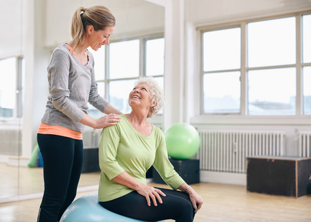 two woman: Female instructor assisting senior woman exercising in health club. Older woman assisted by personal trainer at gym.