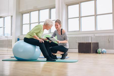 Anciana en una gimnasia que se sienta en bola del ejercicio y hablando con su entrenador personal femenino sobre el plan de ejercicios. Superior de la mujer y el entrenador mirando Informe sobre la salud en conjunto. Foto de archivo - 34387119