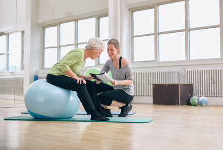 Elderly woman in a gym sitting on exercise ball and talking to her personal female trainer about exercise plan. Senior woman and coach looking at health report together.