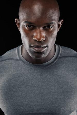 Close-up portrait de jeune homme confiant africain sur le fond noir