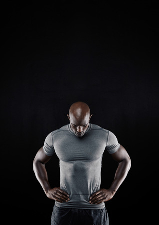 Portrait of muscular young man in sportswear standing with his hands on hips looking down against black background. Strong african athlete.