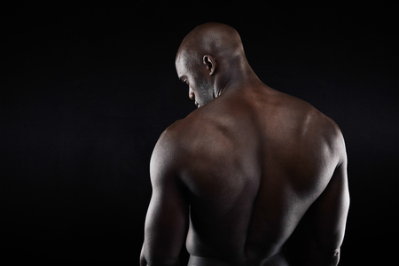 African muscular bodybuilders back on black background. Shirtless fitness model with copyspace. Stock Photo