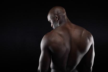 hombres sin camisa: Espalda de culturista musculoso africana sobre fondo negro. Modelo de fitness descamisado con copyspace.