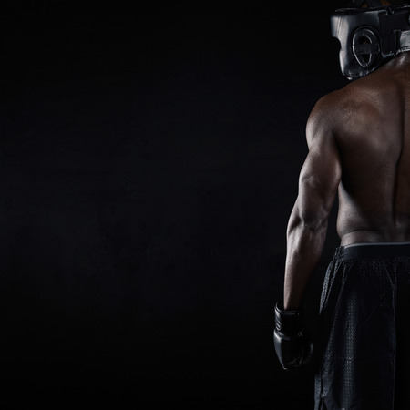 protective gloves: Rear view of muscular young male boxer on black background. Young african male in boxing gear with copy space.