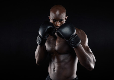 boxeadora: Retrato del boxeador macho rudo posando en la postura de boxeo contra el fondo negro. Luchador profesional listo para combate de boxeo.