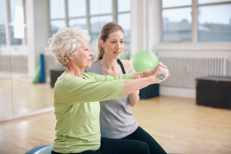 ジムでダンベルを持ち上げるの講師によって支援されている年配の女性。年配の女性がリハビリでパーソナル トレーナーとジムでトレーニングしま 写真素材