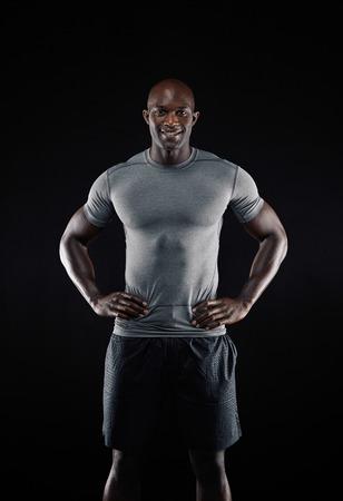 modelos negras: Retrato de hombre feliz africano joven contra el fondo negro. Ajustar joven atleta mirando a la c�mara sonriendo, con las manos en las caderas.